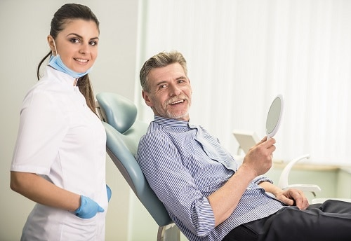 Dental hygienist and man in dental chair