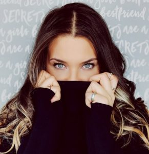 Woman hiding smile with turtleneck shirt