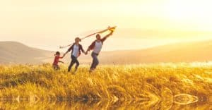 Family holds hands while flying a kite in a field