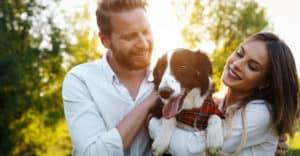 Couple smiling holding dog